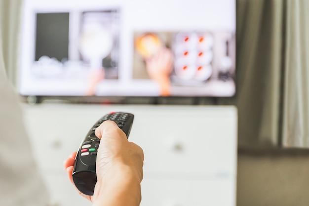 Nahaufnahme der hand, die die fernbedienung des fernsehers hält