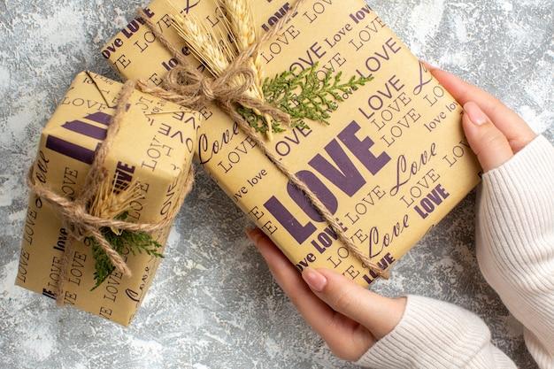 Nahaufnahme der hand, die ein schönes verpacktes geschenk für weihnachten auf der eisoberfläche hält