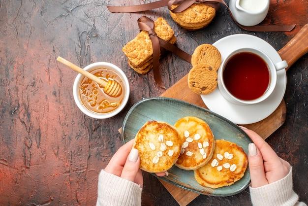 Nahaufnahme der hand, die ein tablett mit frischen pfannkuchen nimmt, eine tasse schwarzen tee auf einem holzschneidebrett honig gestapelte keksmilch auf einer dunklen oberfläche