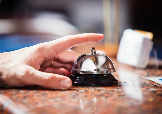 Nahaufnahme der hand, die eine serviceglocke an der hotelrezeption läutet, um aufmerksamkeit zu erregen