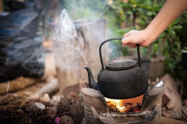 Nahaufnahme der hand, die einen alten wasserkocher mit kochendem wasser auf dem feuer mit einem holzkohleofen auf unscharfem hintergrund hält