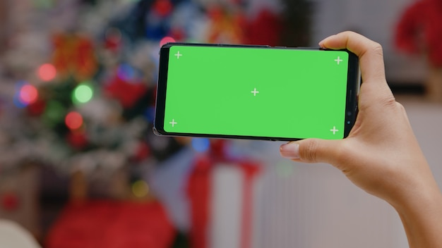 Nahaufnahme der hand, die einen horizontalen grünen bildschirm auf dem smartphone hält