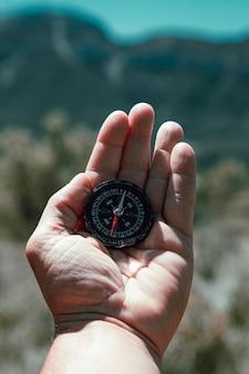 Nahaufnahme der hand, die einen kompass auf dem berg hält