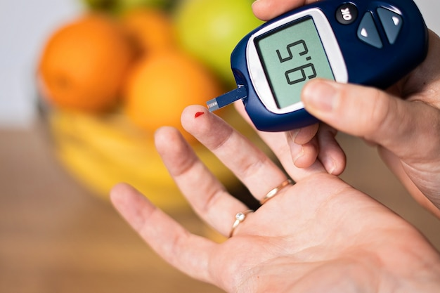 Nahaufnahme der hand, die glukose im blut zu hause misst