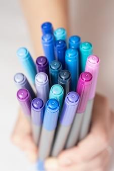 Nahaufnahme der hand, die markierungen verschiedener farben in kalten tönen hält. draufsicht auf verschiedenfarbige markierungen.