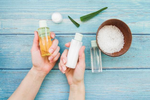 Nahaufnahme der hand die natürliche badekurortsprühflasche auf holztisch wählend