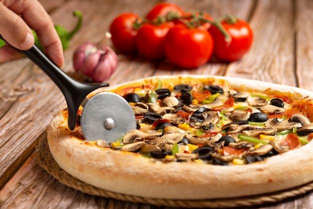 Nahaufnahme der hand, die pizza mit gemüse und peperoni auf holz schneidet