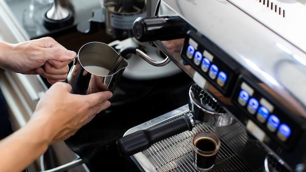 Nahaufnahme der hand, die schlagsahne mit kaffee hält. zubereitung einer tasse kaffee in einer kaffeemaschine, dampf und tasse. espressomaschine mit siebträger hautnah. konzept-kaffeemaschine im café.