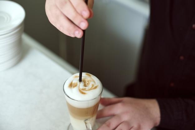Nahaufnahme der hand, die schöne kaffee-latte-kunst macht