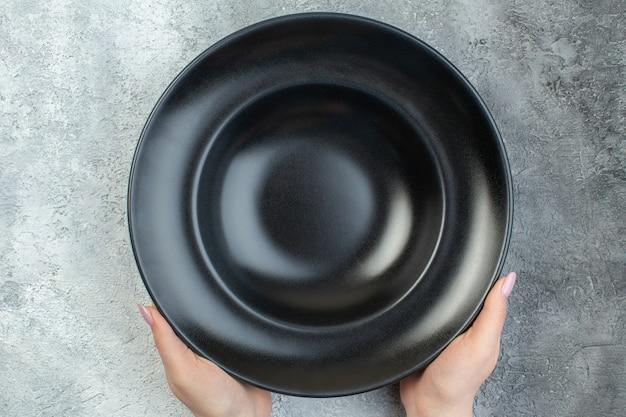 Nahaufnahme der hand, die schwarzes geschirr auf isolierter grauer eisfläche mit freiem platz hält