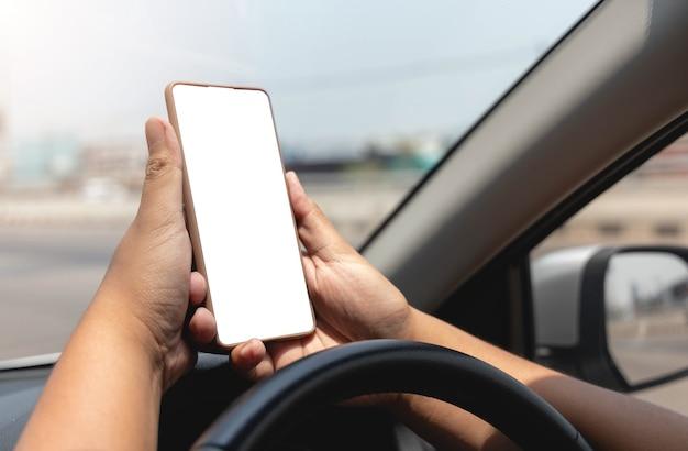 Nahaufnahme der hand, die smartphone mit weißem modell auf bildschirmhintergrund des autolenkrads hält