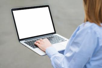 Nahaufnahme der Hand einer Frau, die auf Laptoptastatur schreibt