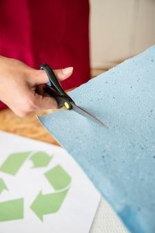 Nahaufnahme der hand einer frau, die blaues papier mit scheren schneidet