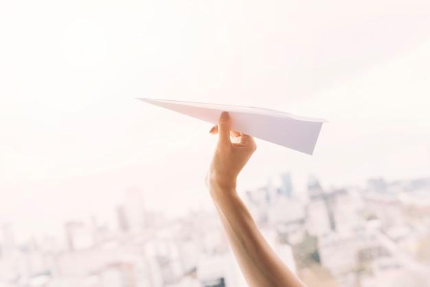Nahaufnahme der hand einer frau, die büttenpapierflugzeug gegen stadtbild fliegt