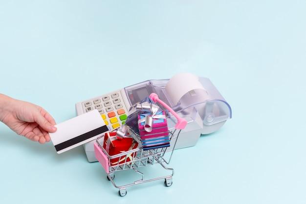 Nahaufnahme der hand einer frau, die eine bankkarte über einem kassenterminal hält, um einkäufe in einem einkaufswagen mit geschenkboxen, seitenansicht, kopienraum zu bezahlen. geschäftskonzept
