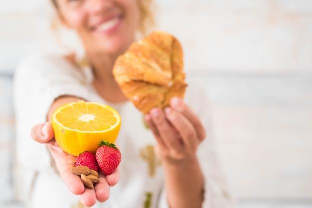 Nahaufnahme der hand einer frau, die eine orange und eine erdbeere hält und in der anderen hand ein croissant - diät und gesunder lebensstil und konzept