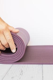Nahaufnahme der hand einer frau, die eine violette yogamatte auf weißem holz entfaltet