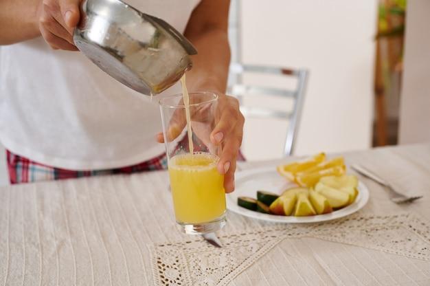 Nahaufnahme der hand einer frau, die frisch gepressten orangensaft von der zitruspresse in ein transparentes glas gießt. frühstück vorbereiten