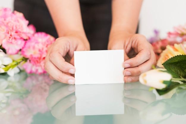 Nahaufnahme der hand einer frau, die leere weiße visitenkarte über schreibtisch hält