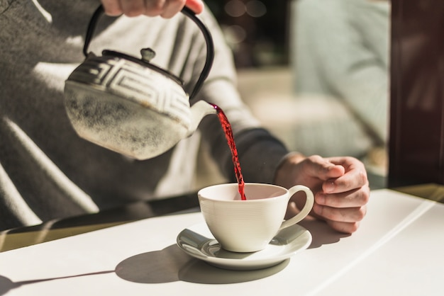 Nahaufnahme der hand einer frau, die roten tee vom traditionellen kessel in der weißen schale gießt