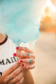Nahaufnahme der hand einer frau mit blauer zuckerwatte