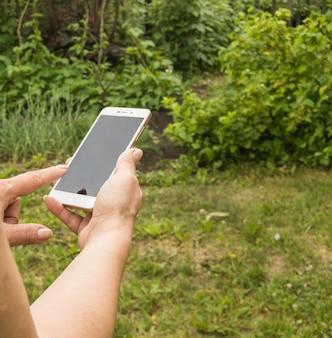 Nahaufnahme der hand einer frau mit einem smartphone, um im sommer eine nachricht vor dem hintergrund von grünem gras im garten zu senden