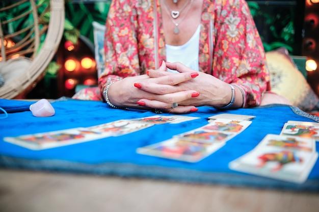 Nahaufnahme der hand einer frau mit tarotkarten, um die zukunft vorherzusagen - esoterisches konzept