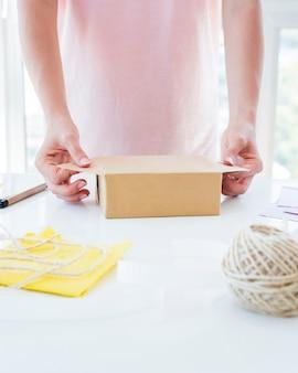 Nahaufnahme der hand einer frau, welche die geschenkbox auf weißer tabelle einwickelt