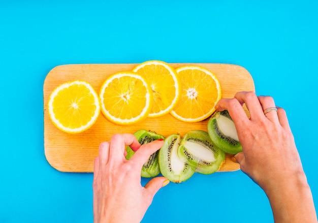 Nahaufnahme der hand einer frau, welche die scheiben der kiwi mit orangen auf hackendem brett gegen blauen hintergrund anordnet