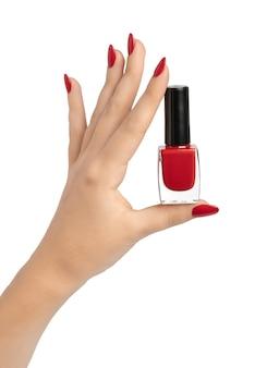Nahaufnahme der hand einer jungen frau mit langer roter maniküre auf nägeln gegen weiß