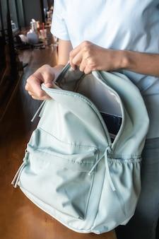 Nahaufnahme der hand einer jungen studentin, die einen blauen rucksack mit habseligkeiten zum college oder zur universität packt. sammeln von sachen für eine reise, urlaub.