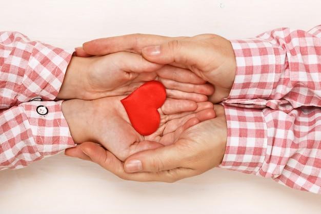 Nahaufnahme der hand einer kleinen tochter und der mutter, die ein herz in ihren palmen zusammenhalten.