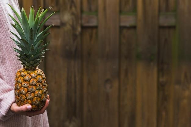 Nahaufnahme der hand einer person, die ananas gegen hölzerne wand hält