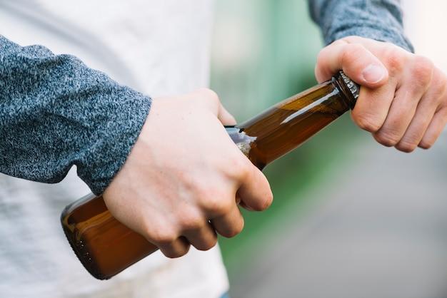 Nahaufnahme der hand einer person, die bierflasche öffnet