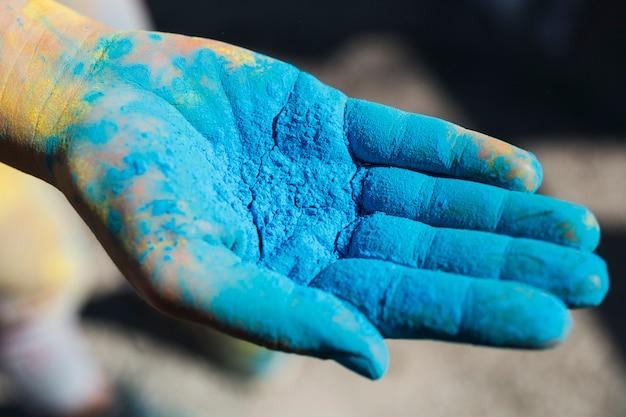 Nahaufnahme der hand einer person, die blaue holi farbe anhält