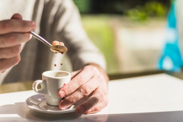 Nahaufnahme der hand einer person, die braunen zucker in den roten kräutertee einsetzt