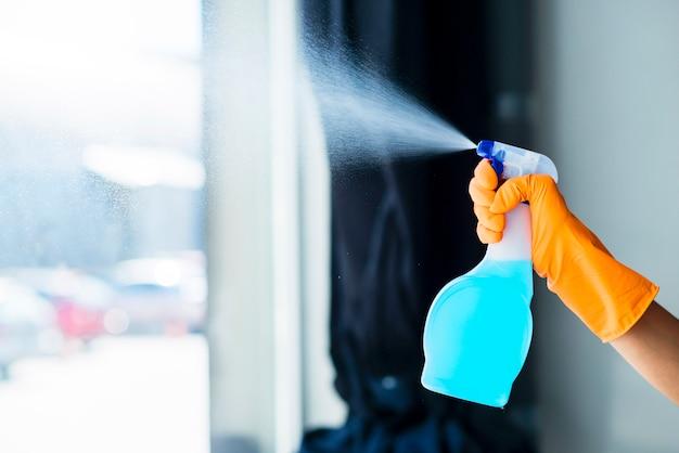 Nahaufnahme der hand einer person, die das flüssige reinigungsmittel auf fensterglas sprüht