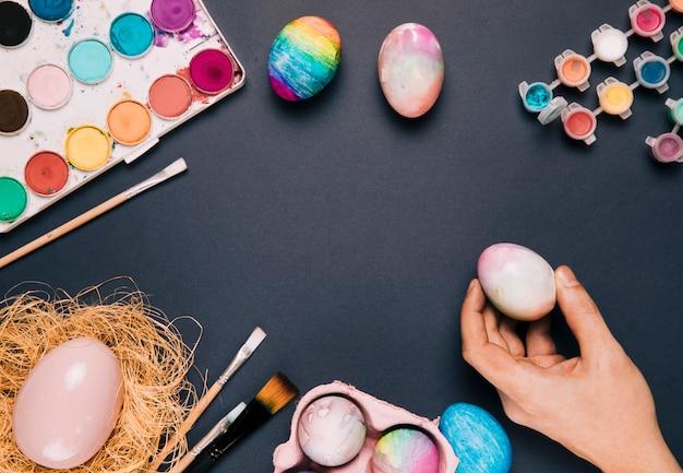 Nahaufnahme der hand einer person, die das gemalte ei mit farbenfarbe und -pinseln auf schwarzem hintergrund hält