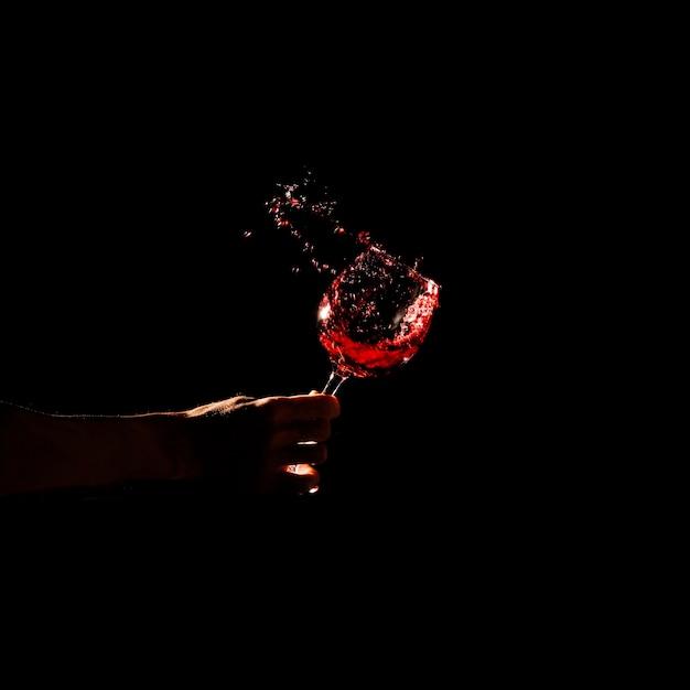 Nahaufnahme der hand einer person, die das glas rotwein spritzt aus glas hält