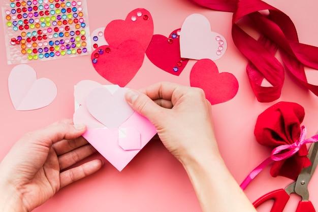 Nahaufnahme der hand einer person, die das herzpapier in den rosa umschlag legt