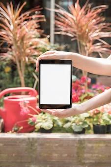 Nahaufnahme der hand einer person, die digitale tablette mit leerem weißem bildschirm hält