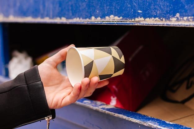 Nahaufnahme der hand einer person, die einen pappbecher in den recyclingbehälter wirft, umweltkonzept, weltumwelttag