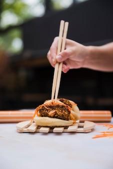 Nahaufnahme der hand einer person, die essstäbchen über dem gekochten mehlkloß mit fleisch- und gemüsefüllung hält