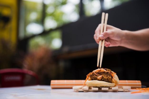 Nahaufnahme der hand einer person, die gua bao mit essstäbchen auf hölzernem behälter isst
