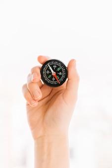Nahaufnahme der hand einer person, die kompass lokalisiert auf weißem hintergrund hält