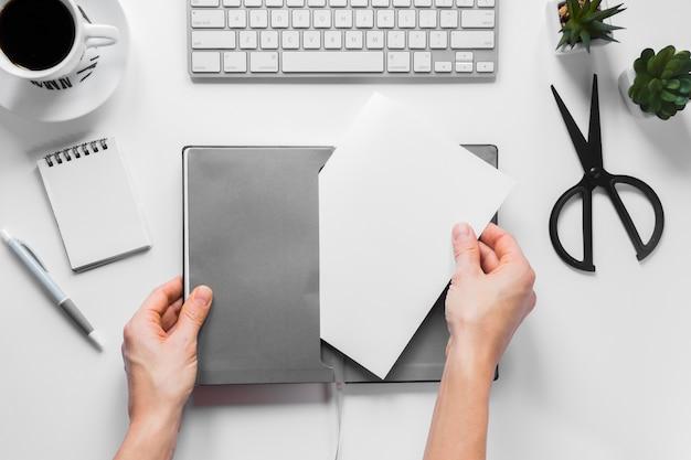 Nahaufnahme der hand einer person, die leeres weißbuch in die graue abdeckung auf arbeitsplatzschreibtisch einfügt