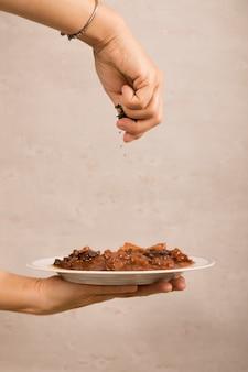 Nahaufnahme der hand einer person, die mexikanischen rindfleischgericht schmückt