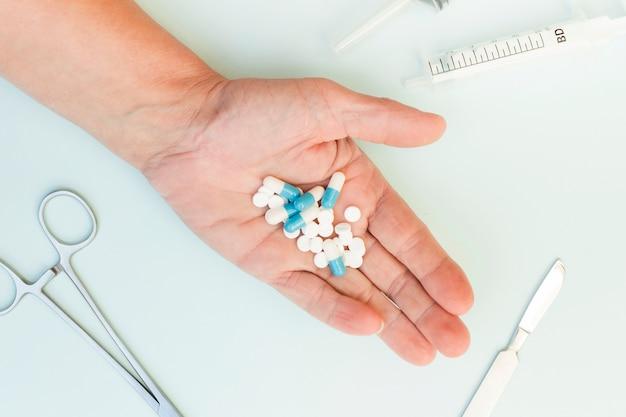 Nahaufnahme der hand einer person, die pillen mit medizinischen instrumenten auf weißem hintergrund zeigt
