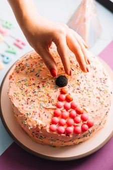 Nahaufnahme der hand einer person, die schokoladenball auf verziertem kuchen hält