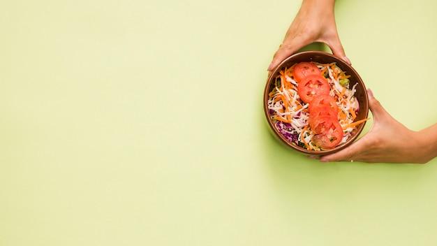 Nahaufnahme der hand einer person, die schüssel salat auf tadellosem grünem hintergrund hält